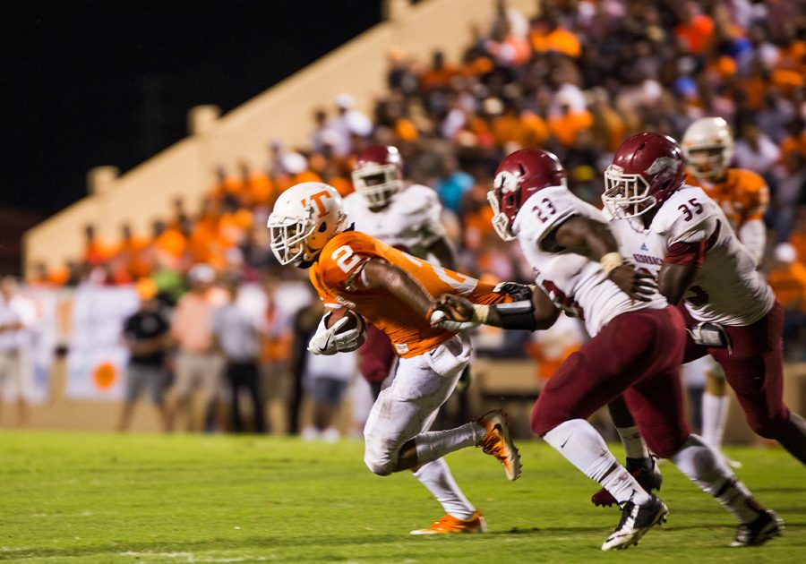 Receiver Quan Hampton pulls away from the defenders during the Texas vs. Arkansas game. The Tigers defeated the Razorbacks 37-7.