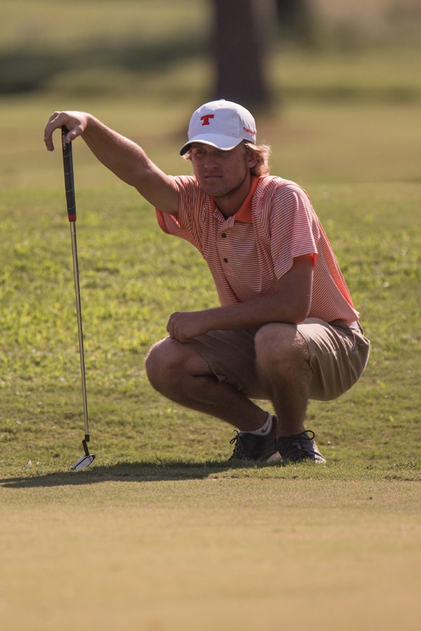 Junior Matt Preiskorn lines up a putt during the City Golf Tournament. The Varsity Boys golf team competed in the tournament on September 14.