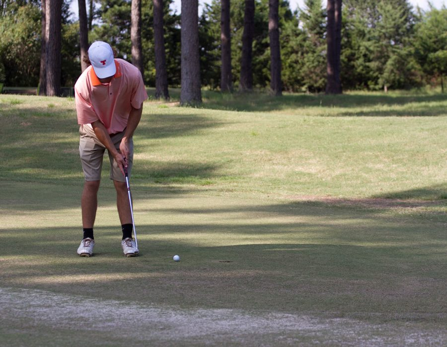 Senior Alex Davis putts the ball during the City Golf Tournament. The Varsity Boys golf team competed in the tournament on September 14.