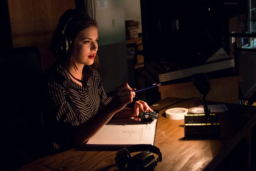 Madison Sutton dons headphones for communication with crew as she works in the technical booth. Sutton has served as stage manager in many theater productions.