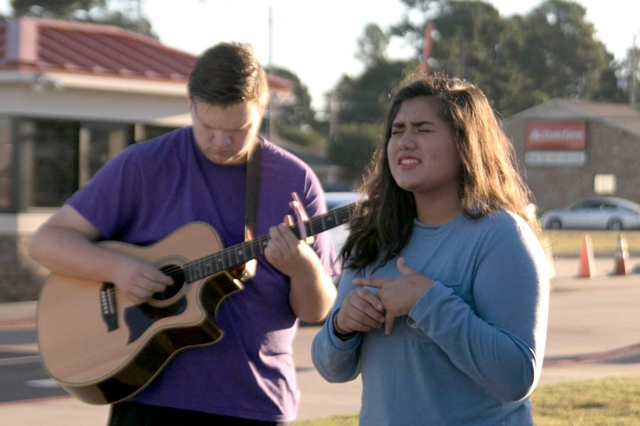 Senior Yvonne Arias sings as junior Colin Runnels plays his guitar at the annual See You at the Pole.