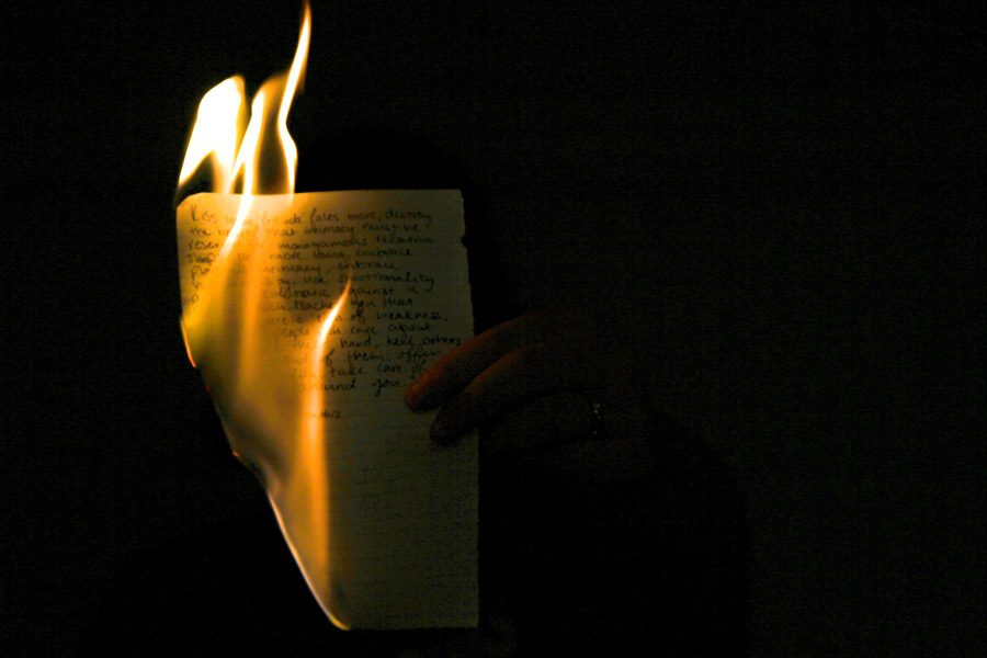 Flames consume a page of her journal. She has kept a journal for all four years of high school to help her cope with her father's alcoholism and her brother's drug addiction.