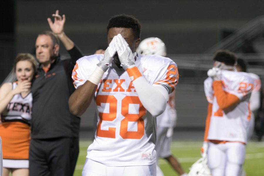 Senior D'Andre Purifoy and other players wipe tears from his eyes while coach Barry Norton leads the team during the playing of the school song after the Tigers were defeated in the playoff game against West Mesquite. The Texas High Tigers end their season with a record of 10-1.