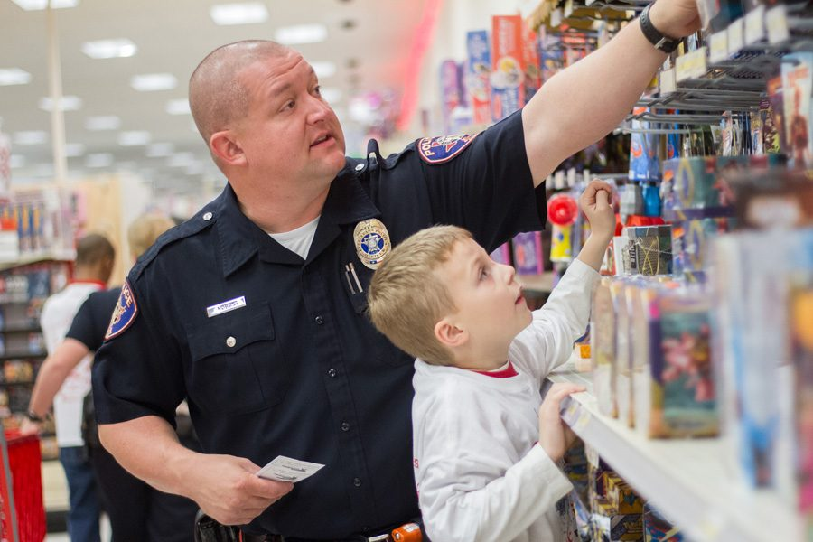 Officer Hobbs assists a child with getting a toy that's out of reach. The annual Shop with a Cop was held on Dec 6 at Target where 103 students were able to receive an early Christmas from local police and firefighters.