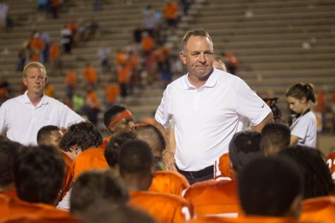Barry Norton addresses football players after a 2014 game.