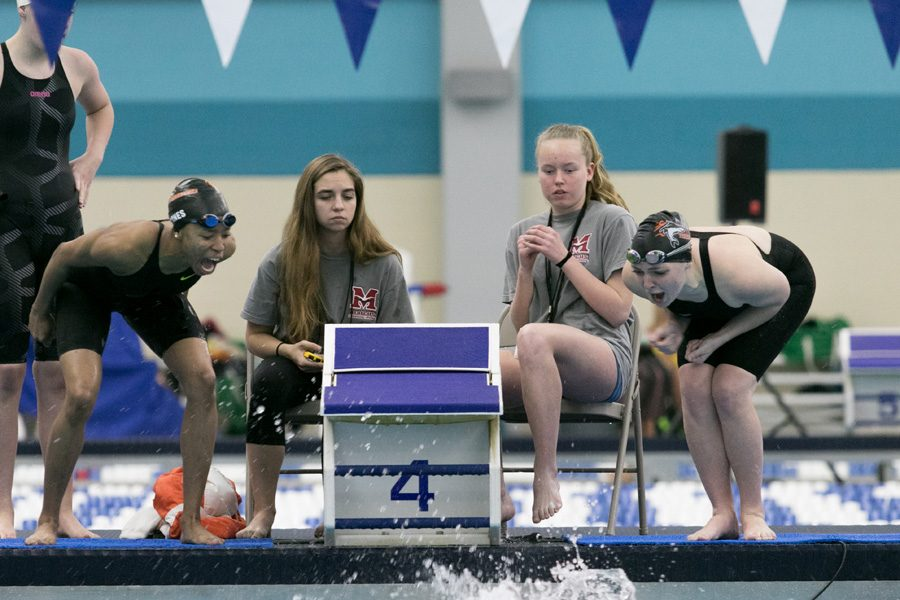 Seniors Cathryn Payne and Ohema Barnes cheer on a teammate during the Regional swim meet. The Texas High Tigersharks will compete in the State swim meet on February 17-19.