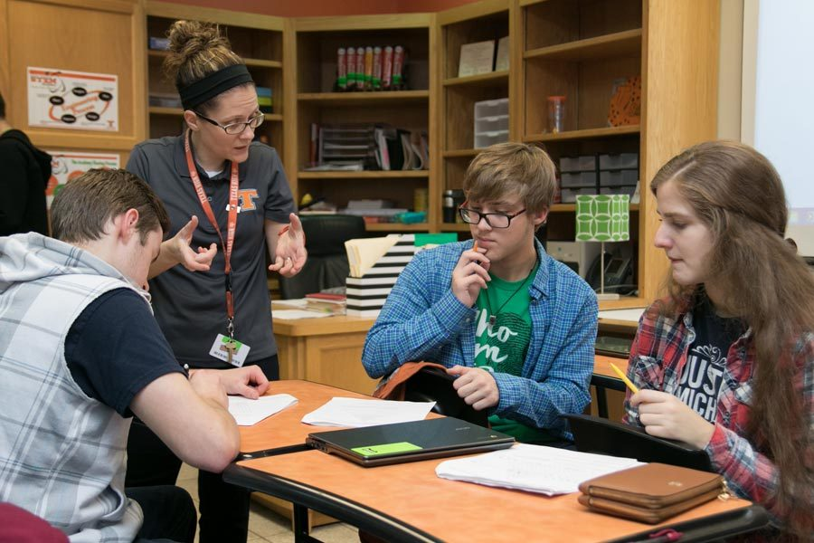 Mrs. Ayers helps a group of students during class. Ayers left her job as a chemical engineer to become a teacher.