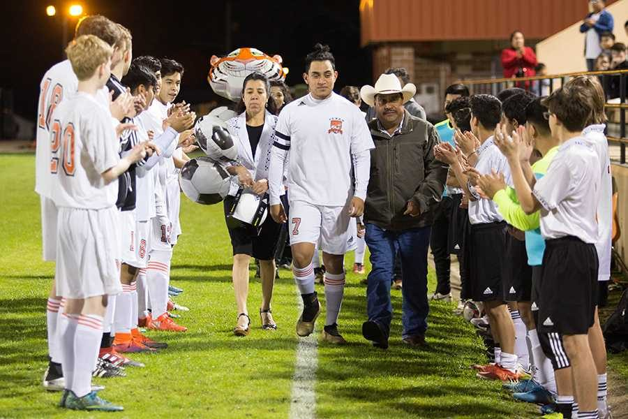 During the boy's soccer senior night, senior Isidro Hernandez walks out with his family.