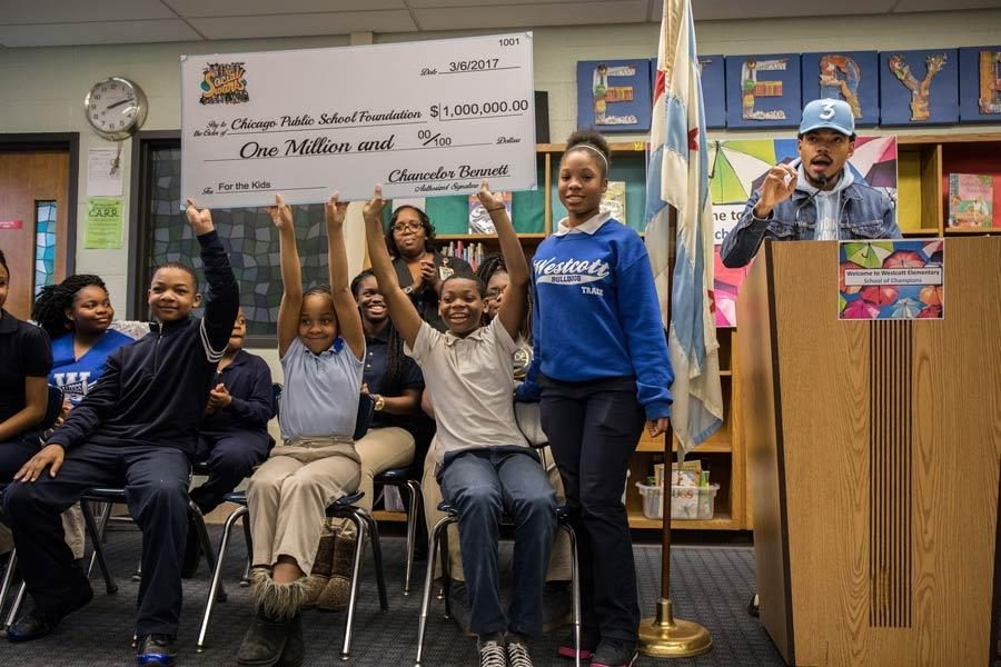 Students hold up a check for $1 million dollars from Chance the Rapper, right, who holds a press conference at Westcott Elementary School in Chicago's Chatham neighborhood on March 6, 2017. Photo by Zbigniew Bzdak
