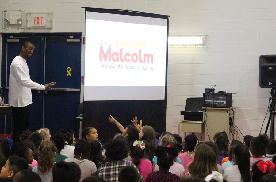 Malcolm Mitchell greets students at Highland Park Elementary. The Read with Malcolm program was founded to encourage children to read.
