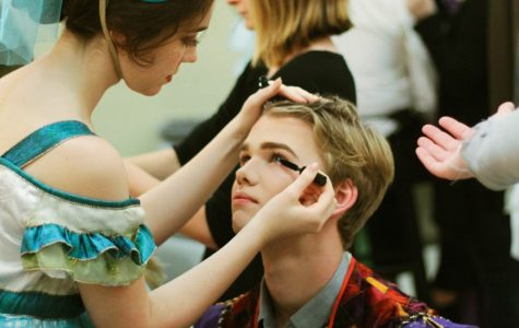 """Junior Colton Johnson receives help from senior Grace Hickey with putting on his stage makeup. Johnson played the role of Pascal in """"The Axeman's Requiem."""" Photo by Odin Contreras"""