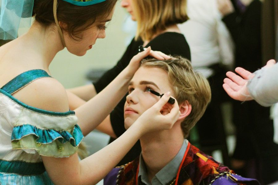 "Junior Colton Johnson receives help from senior Grace Hickey with putting on his stage makeup. Johnson played the role of Pascal in ""The Axeman's Requiem."" Photo by Odin Contreras"