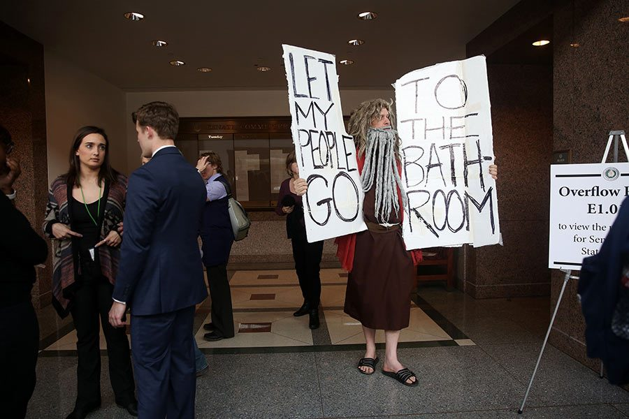 John Erler, dressed as Moses, holds signs as members of the Senate State Affairs Committee debate and hear public testimony over Senate Bill 6, the transgender bathroom bill, on Tuesday, March 7, 2017 at the Texas State Capitol in Austin, Texas. The bill would require transgender Texans to use public restroom facilities that match their birth gender. (Rose Baca/Dallas Morning News/TNS)