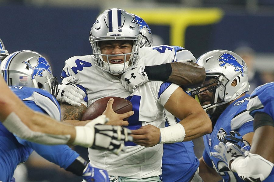 Dallas Cowboys quarterback Dak Prescott (4) struggles to break away from the Detroit Lions defense for a short gain Monday, Dec. 26, 2016 in AT&T Stadium in Arlington, Texas. (Brad Loper/Fort Worth Star-Telegram/TNS)