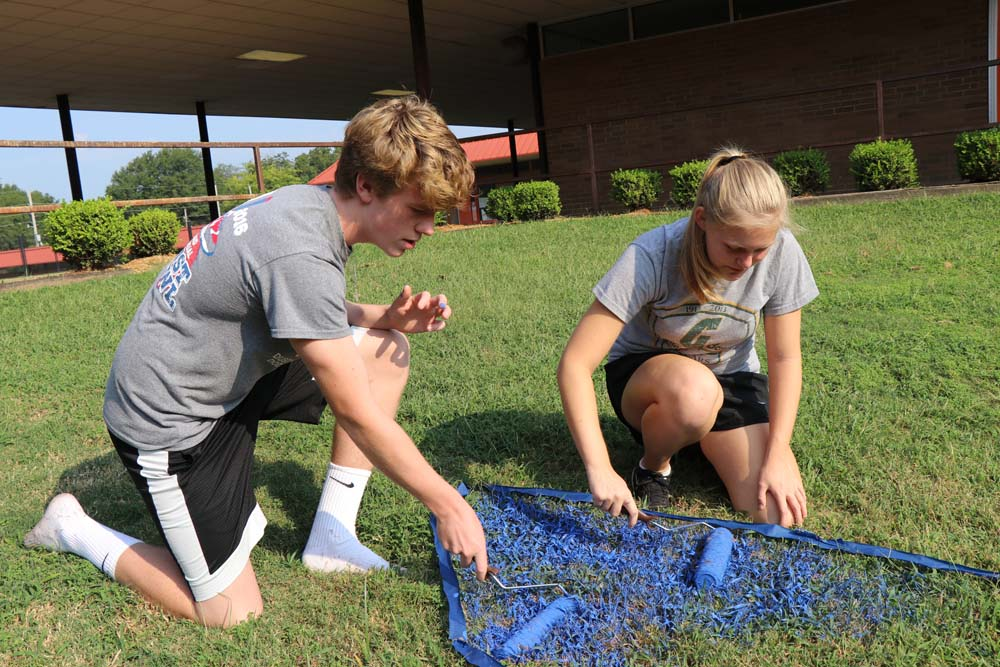 Sophomores Jackson Cheney and Sarah Lingle work together to paint the pit, which is located outside the cafeteria.