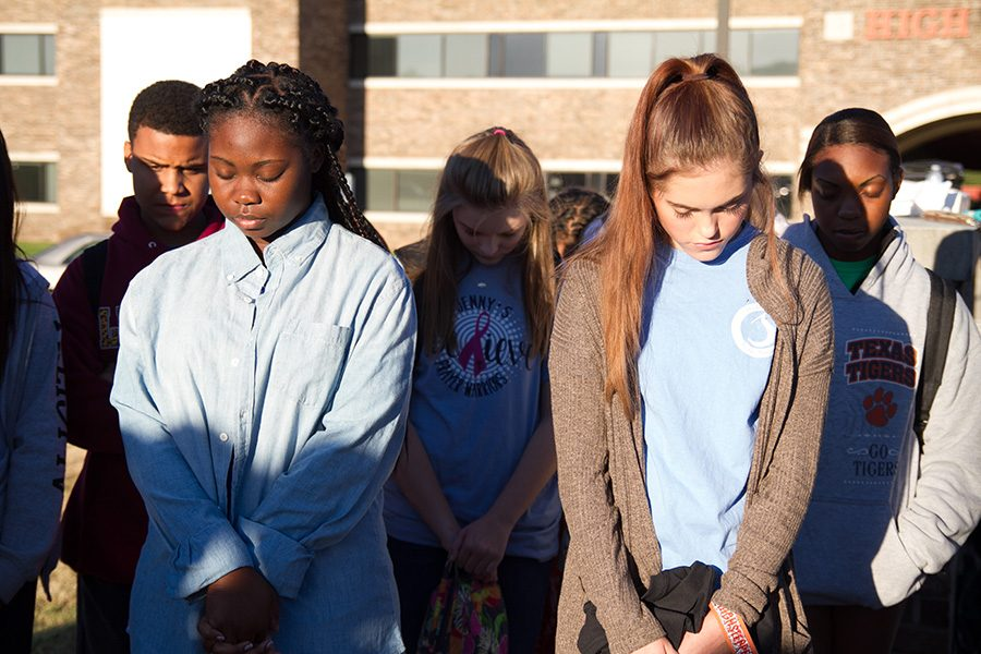Students bow their heads in recognition of the national prayer movement.