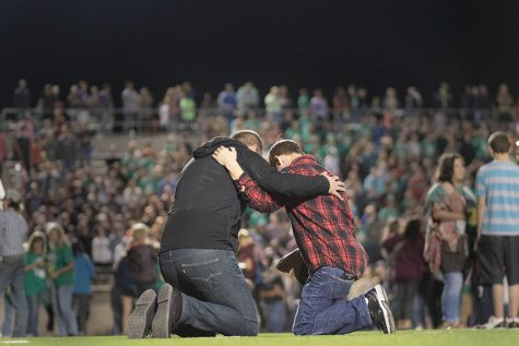Students and leaders kneel together to pray at Fields of Faith, which happened on oct. 11 at the Pleasant Grove High School football field.