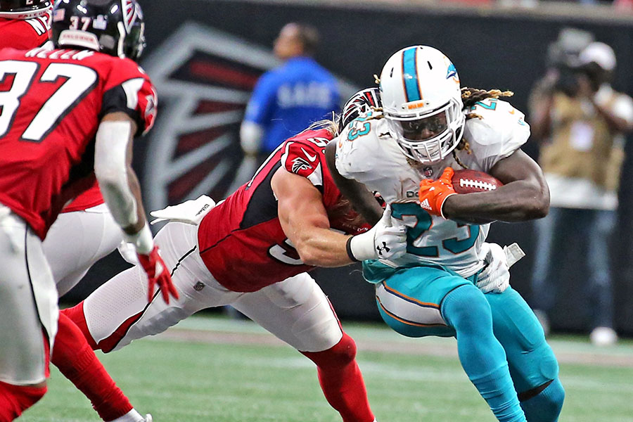Miami Dolphins' Jay Ajayi (23) runs the ball in the fourth quarter as Atlanta Falcons' Brook Reed (50) reaches to tackle him on Sunday, Oct. 15, 2017 at the Mercedes-Benz Stadium in Atlanta, Ga. The Dolphins have traded Ajayi to the Philadelphia Eagles for a fourth-round draft pick. (Charles Trainor Jr./Miami Herald/TNS)