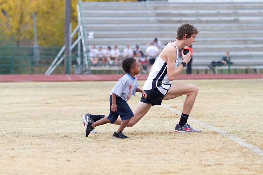 Senior Jonathan Green warms up for the annual Dash 4 Cash, while a participating child follows behind.