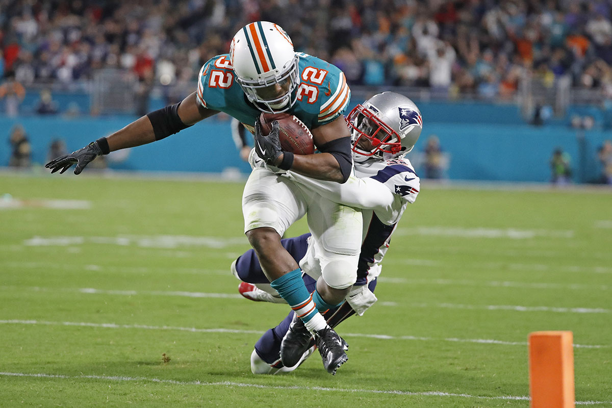 Miami Dolphins running back Kenyan Drake (32) runs towards the goal line as New England Patriots free safety Devin McCourty (32) gives chase in the second quarter as the Miami Dolphins host the New England Patriots at Hard Rock Stadium Monday, Dec. 11, 2017 in Miami Gardens, Fla. (Al Diaz/Miami Herald/TNS)