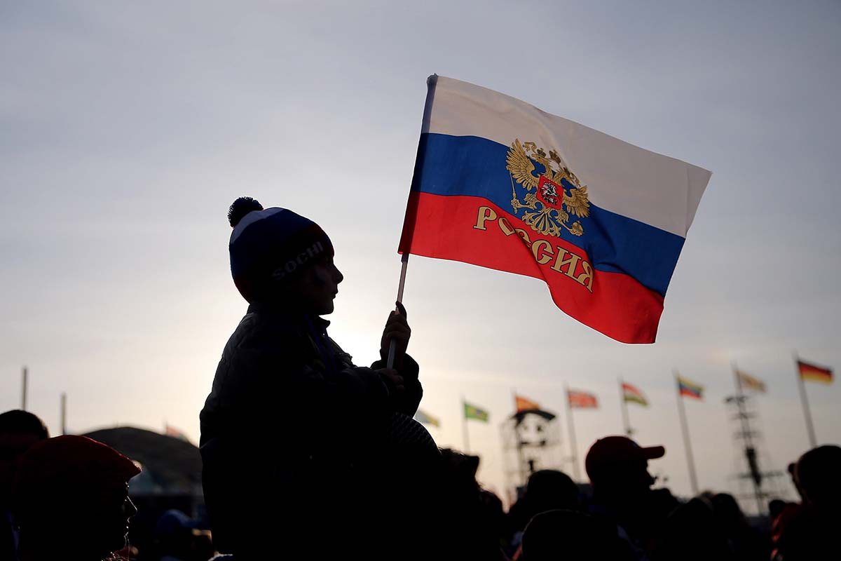 A boy waves a Russian flag in Olympic Park at the Winter Olympics in Sochi, Russia, on Wednesday, Feb. 19, 2014. The International Olympic Committee has banned Russia from competing in the 2018 Winter Olympics in Pyeongchang, South Korea. (Brian Cassella/Chicago Tribune/TNS)
