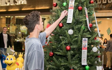 Freshman Cort Rainwater places an 'angel' card on the Salvation Army Christmas donation tree. Applications to sign up end today.