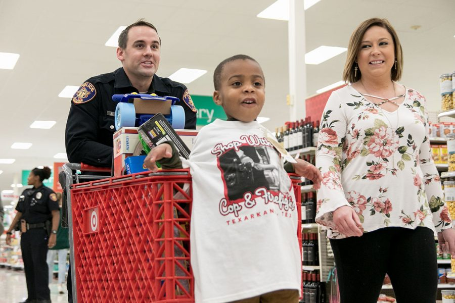 A child riding in the buggy is all smiles as Texarkana Texas Police officer Aaron Lewis pushes them toward the toy aisle at Target on Dec. 5, 2017. The annual Shop with a Cop and firefighter event provided Christmas toys to underprivileged children in the Texarkana area.
