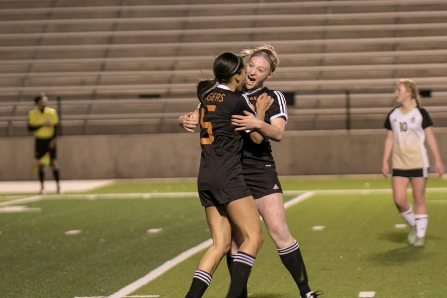 Junior Kendyl Myers and senior Chloe Coake embrace after the Tigers score their first goal.