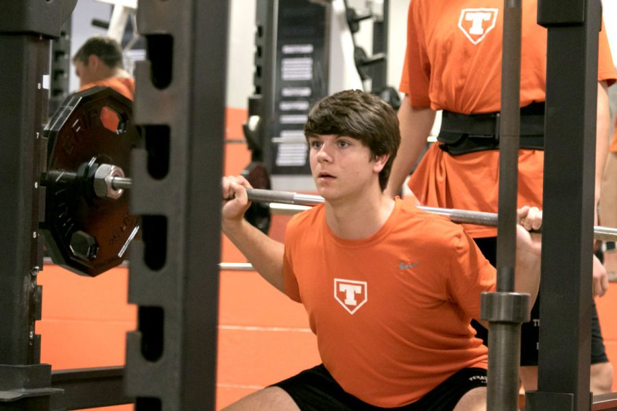 Sophomore+Michael+Sikorski+squats+with+the+help+of+his+partner+during+his+athletic+period.+All+baseball+teams+are+doing+weight+training+this+year+as+a+part+of+their+program.+