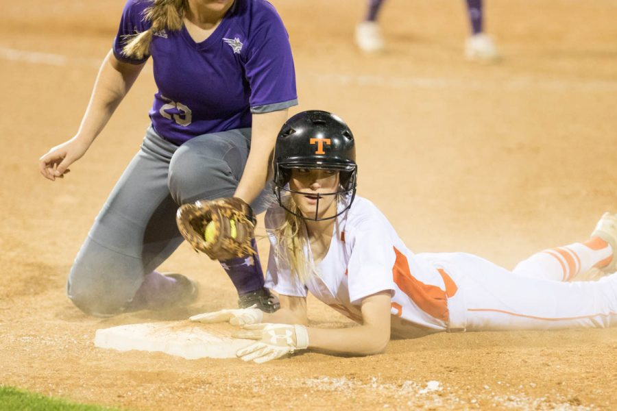 As the dust settles, senior Ryann Williams waits for the call from the umpire. Williams dove head first back to first base when the Hallsville catcher tried to throw her out. Tigers lost their home opener 9-7.