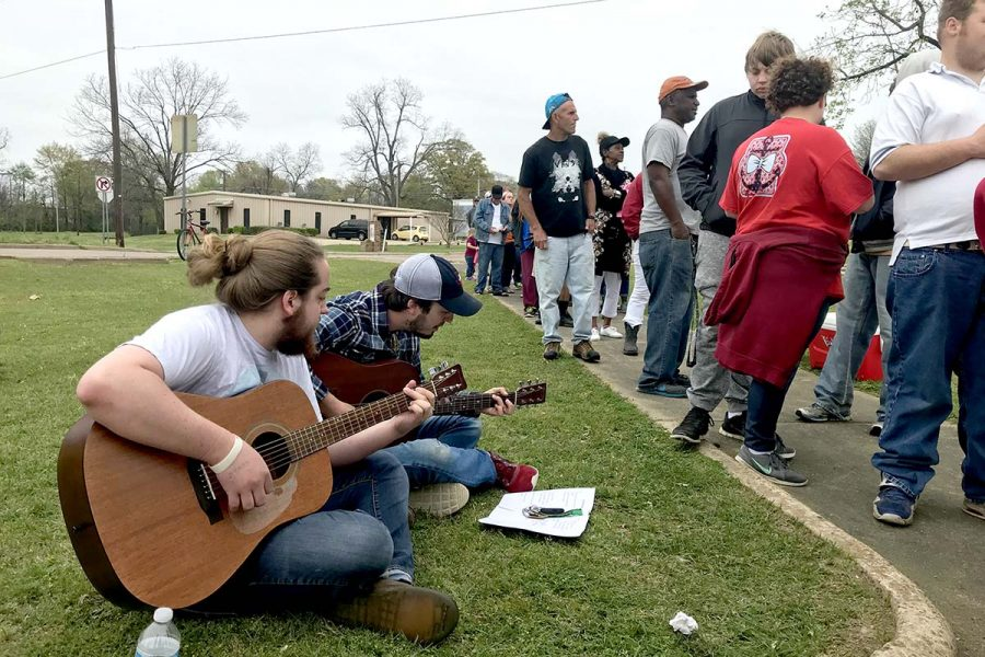 Musicians Hudson Davis and Mark Meadows sit on the grass and play worship songs. They volunteered to play music at a Christian Warriors outreach event on March 25, which was aimed to help feed the homeless. They do this once a month, and partner with other churches as well.