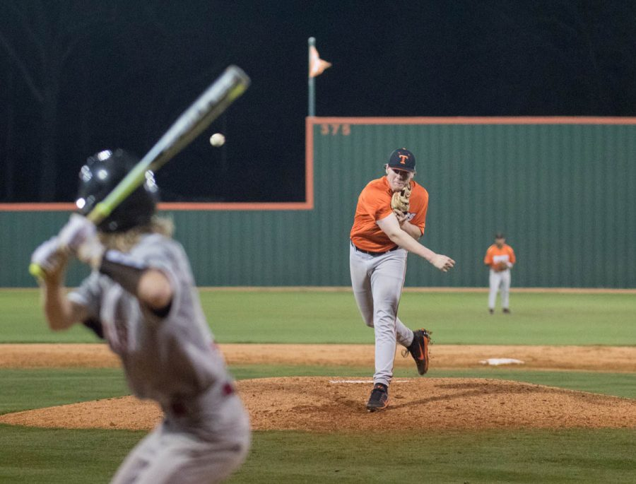 Amidst the cheers of teammates and dust filled air, Junior Walker Davis throws the ball resulting in a strike out.
