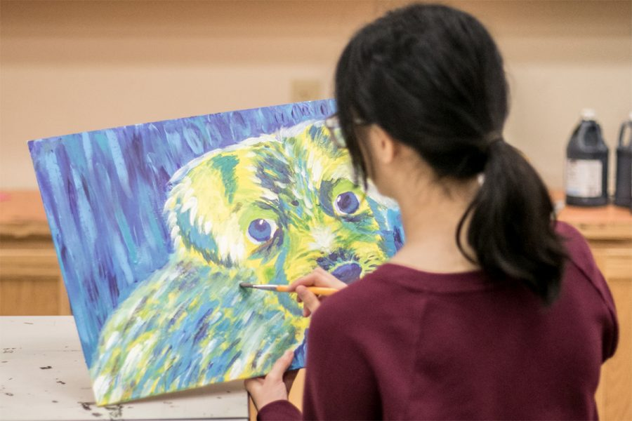 Junior Victoria Van paints a  dog in vivid colors to be donated to the local animal shelter.