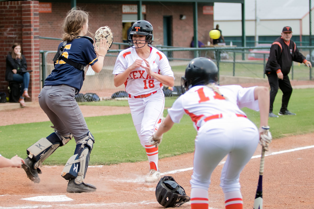 Sophomore Alexis Bolden prepares to collide with the catcher as senior Ryan Williams yells for her to slide into home plate. Bolden would score a 4-2 victory over Pine Tree.