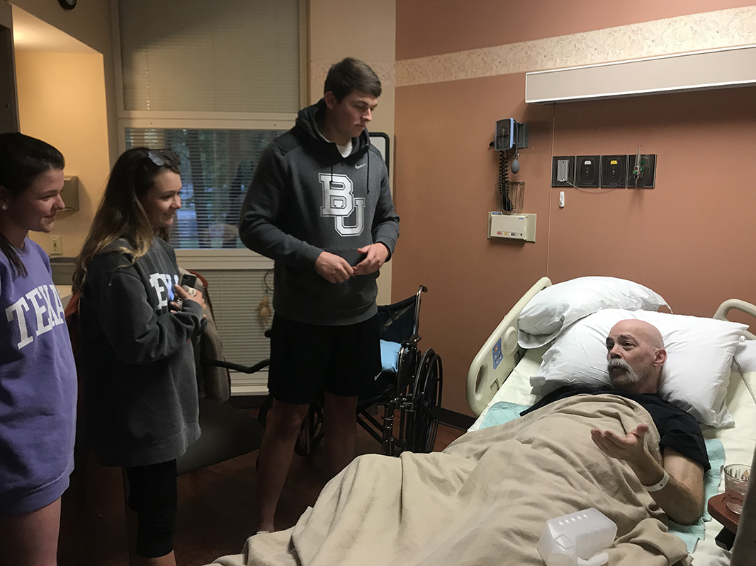 Government teacher John P. Littman talks to seniors Addison Rogers, Sarah Stark and Logan Snell at the hospital. Littman experienced a stroke a month ago, and later received the news that he now has stage four cancer. Submitted photo