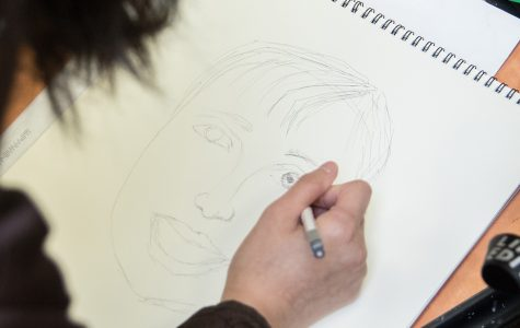 Art Club members draw portraits of children from an orphanage in Afghanistan to send back to them for the Memory Project. Portraits will be sent in May.