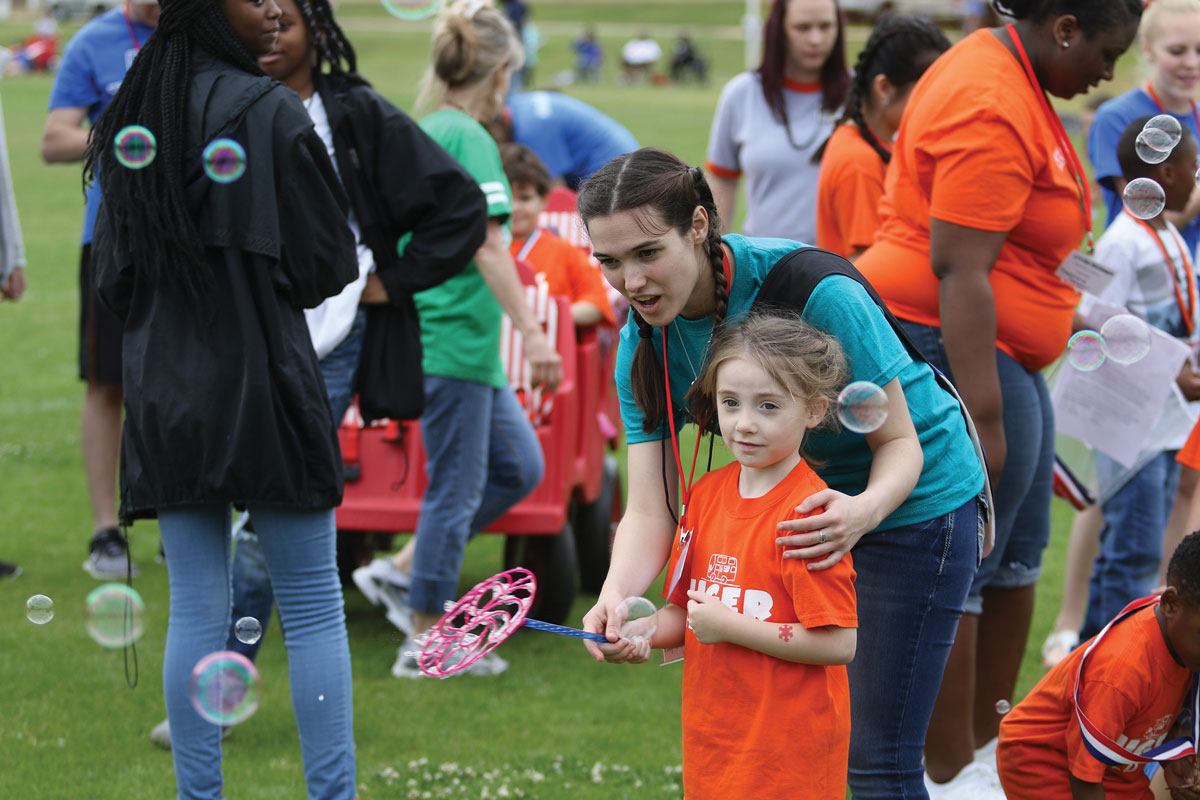 Junior Brittany Kile helps a student make bubbles. The Tiger Strong Field Day was held on May 1.