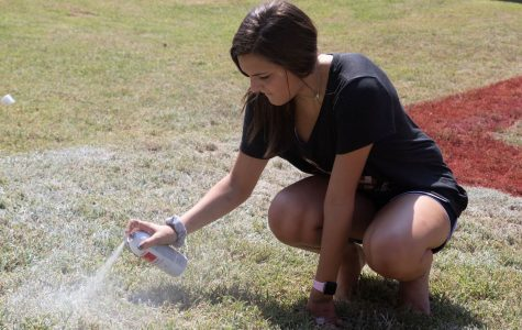 Sophomore Madisyn Givens spray paints the pit. Givens is continuing a Texas vs Arkansas tradition.