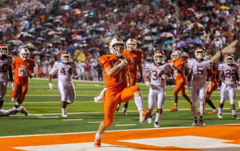 Quarterback Colton Clack high steps into the end zone with Razorbacks trailing behind him. Clack lead the Tigers in a come from behind victory against the Razorbacks.