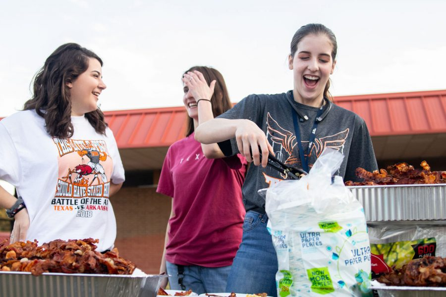 Seniors Mckenzie Brown, Sarah King and Meagan Brown help serve bacon at the annual Bacon Fry that was held on the morning of September 7th in the Texas High School courtyard.