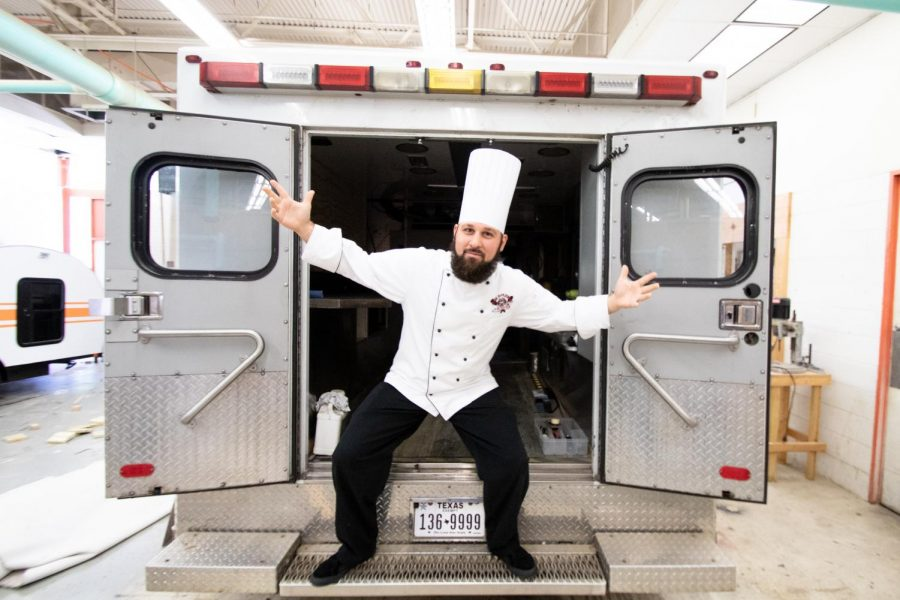 Culinary arts instructor Cory House stands in the back of the old TigerVision ambulance showing his excitement about the opportunity to turn the ambulance into a food truck. TigerVision received a new ambulance, and the culinary department hopes    to raise $10,000 to convert it to a food truck.