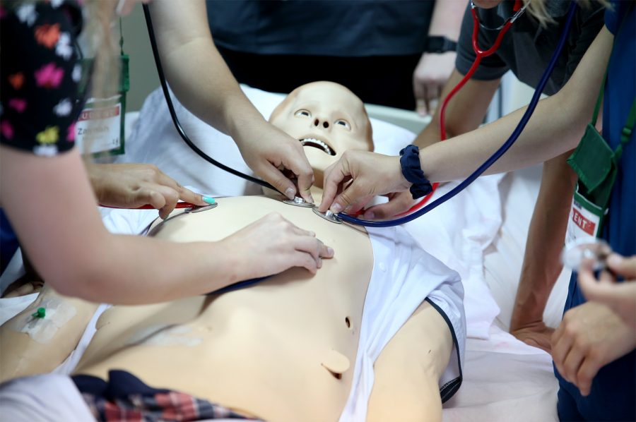 Multiple students surround a mannequin and look for vitals such as heart rate using stethoscopes.
