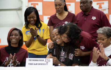 Family members of senior Treyaunne Rush congratulate her as she signs her letter of intent to Texsa A&M University. Four seniors signed with their respective colleges to further their athletic careers.