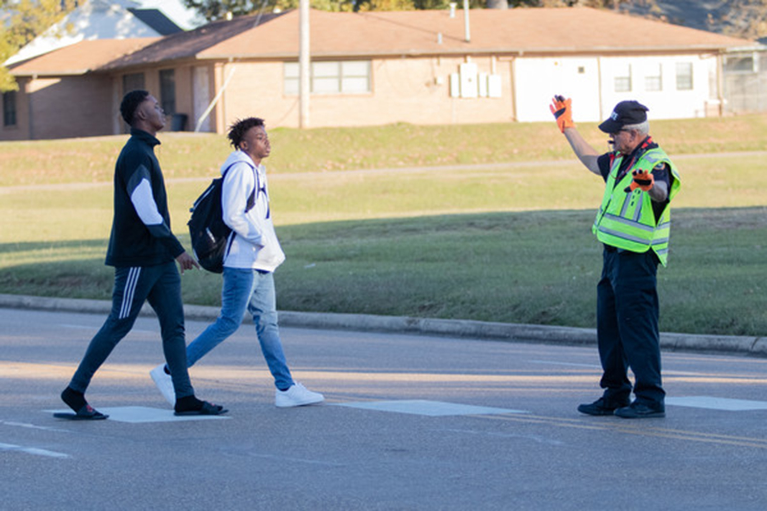 Traffic controller Keith Davis stops the flow of traffic to allow two students to cross the street. Davis has worked for Texas High for the last five years.
