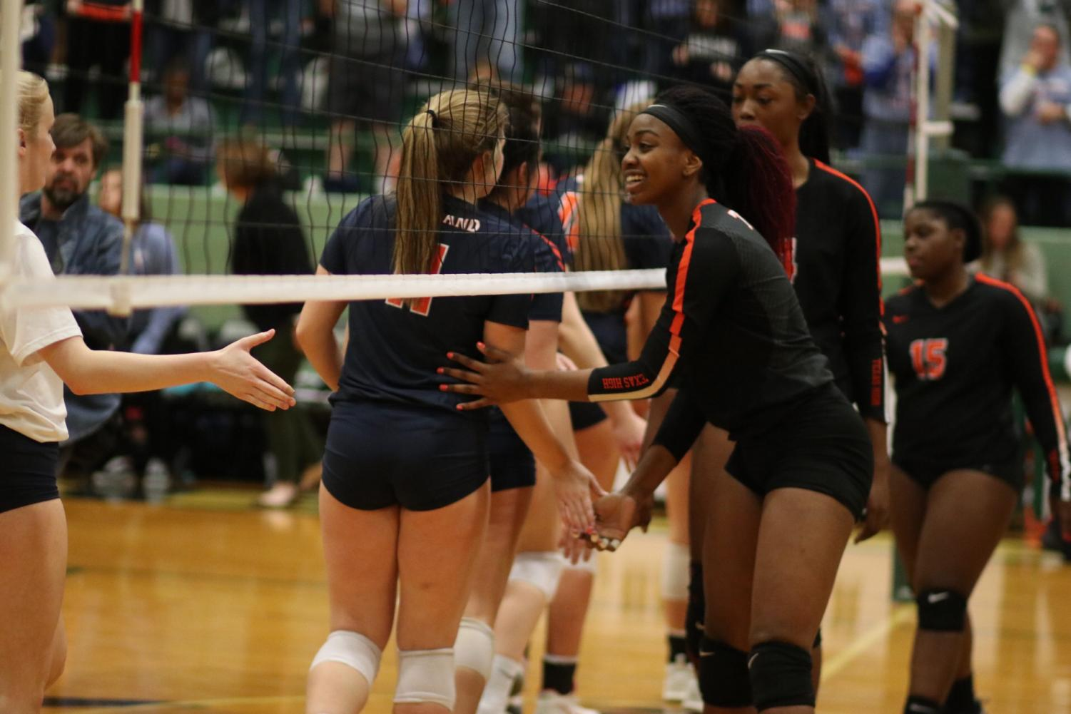 The Lady Tigers wish the Wakeland Wolverines good luck as they begin their first set. Texas High lost the regional semifinals in three sets after advancing in a historic season.