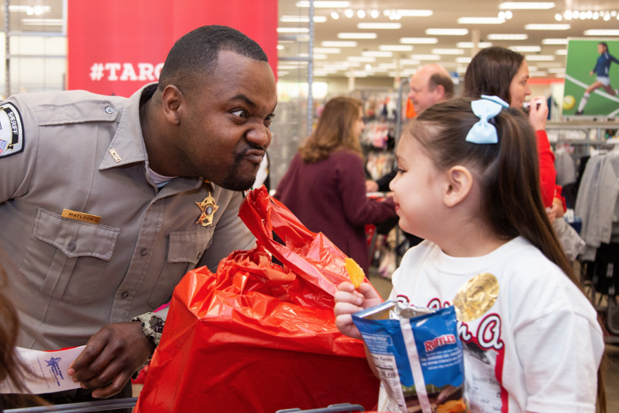 Police officers accompany children at Target as they buy toys. Shop with a Cop was held at Target on Dec. 4.