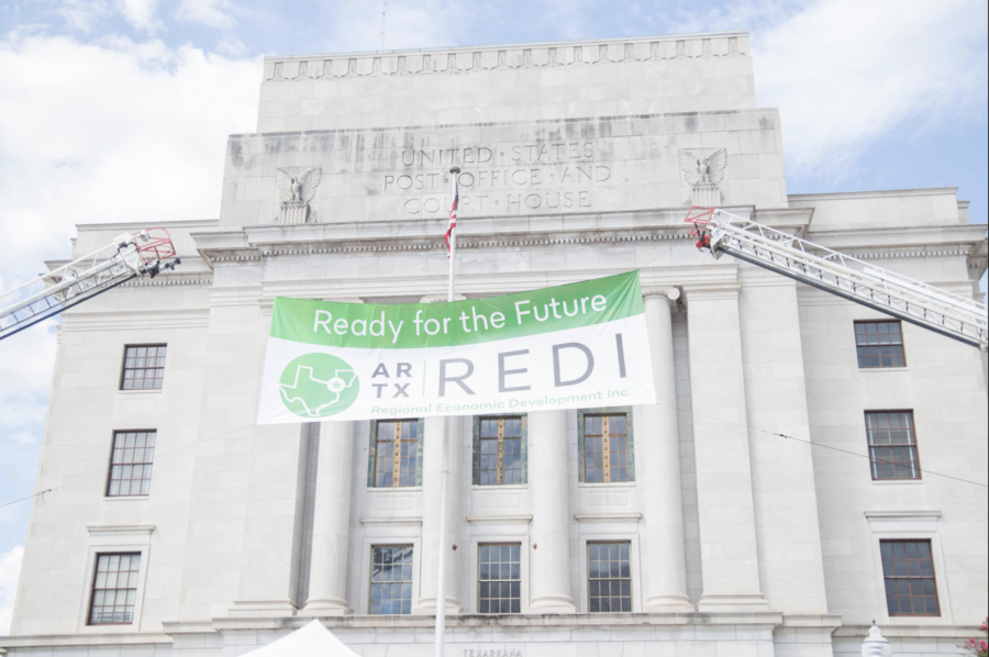 A banner hangs in front of the downtown Texarkana courthouse at the launch event for the Regional economic development initiative, or REDI.  State legislatures and governors from both Texas and Arkansas as well as city officials attended the launch event in September.
