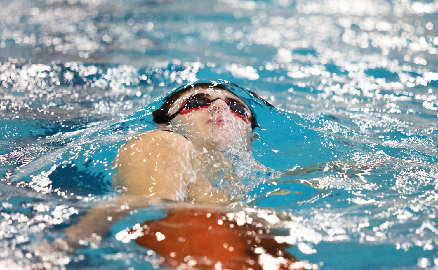 Senior Trent Foster swims in the 100 yard backstroke. Foster placed nine out of 16 in the event.