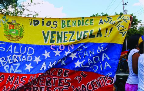 People in the streets protest for peace and liberty from an oppressive government in Venezuela. The country has faced an economic crisis and rampant inflation, leaving many of its citizens in poverty.