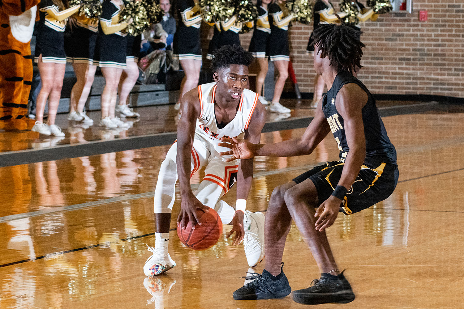 A Tiger basketball player looks to rush away from a Mount Pleasant defender. The Tigers defeated the Mount Pleasant Tigers 58-55.